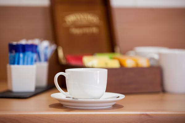 Coffee cup with tea and sugar on table
